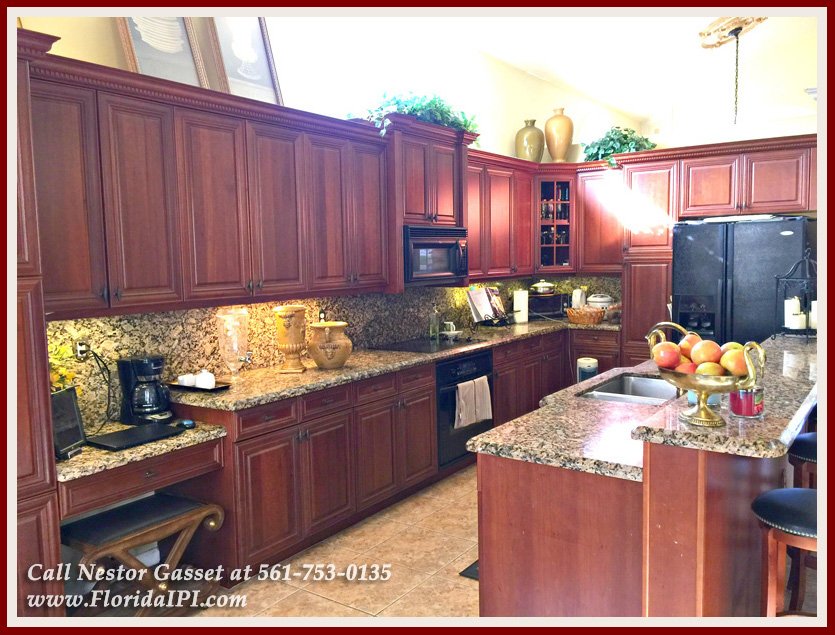 Homes For sale Olympia Wellington Fl 33414 - The gourmet kitchen of this home for sale in Olympia in Wellington FL has granite countertops, beautiful cabinets, a kitchen island, and a breakfast bar!
